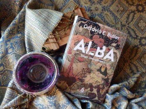 """Ejemplar físico de """"Alba"""" sobre unas telas, una pieza de madera y otra redonda con colores galácticos"""