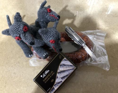 Aparece un peluche de ganchillo (un perro de tres cabezas), un chorizo, una navaja y una lata de sardinillas.