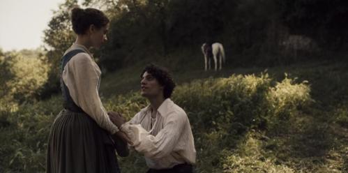 Un personaje masculino en actitud romántica, arrodillado frente a un personaje femenino de la serie. Están en medio del campo y al fondo se ve un caballo blanco.