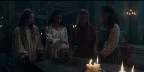 Un grupo de mujeres realizan lo que parece un ritual en algún escenario de interior. Una de ellas tiene la mano sobre una bola que parece de pelusa.