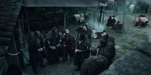 Un grupo de personas están reunidos en lo que parece la plaza de una aldea o un corral. Algunos llevan máscaras.