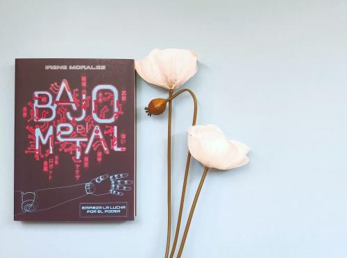 Aparece el libro sobre una superficie blanca junto a unas flores blancas.