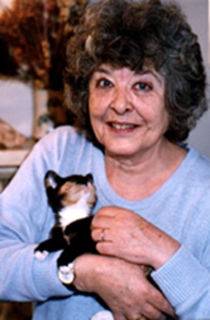 La fotografía no tiene mucha calidad, parece tomada en los años ochenta. La autora ya es una mujer mayor, con canas. Está sonriendo y el gatito se gira para mirarla a la cara.