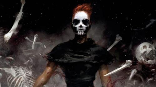 Una figura vestida de negro, con la cara pintada como una calavera, gafas de sol y pelo rojo corto, avanza al frente con gesto desafiante rodeada de huesos y esqueletos