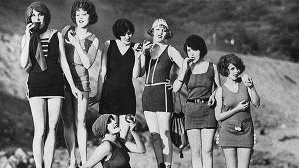Fotografía en blanco y negro donde un grupo de mujeres aparecen en la playa, con trajes de baño de los años 20, posando con manzanas y sonriendo.