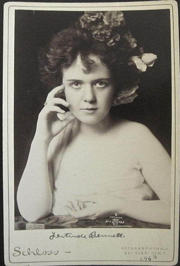 Fotografía muy antigua, casi parece del siglo XIX, con la autora mirando a cámara. Parece bastante joven y lleva un tocado de flores.