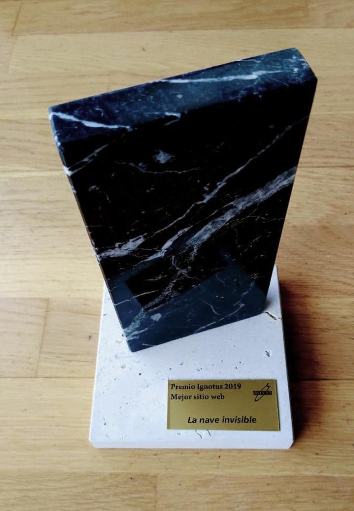"""Monolito de mármol negro con vetas blancas sobre una base blanca con una plaquita dorada que reza: """"Premio Ignotus 2019. Mejor Sitio Web. La Nave Invisible"""" con el antiguo logo de Pórtico (una media luna al final de una órbita bajo un cartel con las siglas AEFCFT)"""