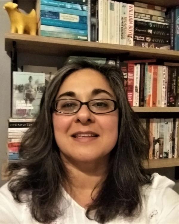 Fotografía de la autora, una mujer de mediana edad, morena de piel y pelo (aunque este está veteado de canas). Lleva unas gafas de montura negra.